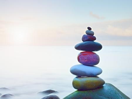Evenwichtige steenpyramide op kust van blauw water van oceaan. Blauwe lucht in spiegel op waterniveau. Slechte lichtomstandigheden. Stockfoto