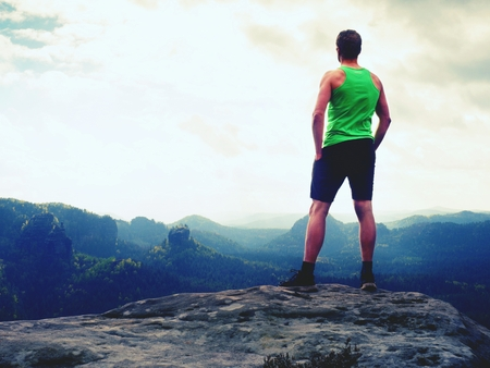 Man in t-shirt and pants. Tourist on mountain peak looking into misty landscape.