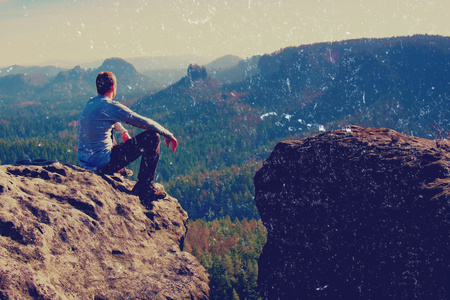 Film grain effect. Young man in black sportswear is sitting on cliffs edge and looking to misty valley bellow Reklamní fotografie
