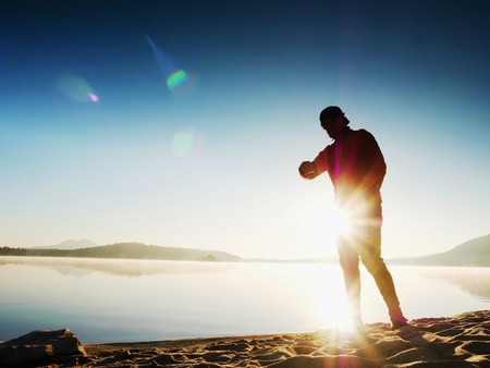 Sports man checking time on his sports watch. Runner at mountain lake exercising against to evening sun.