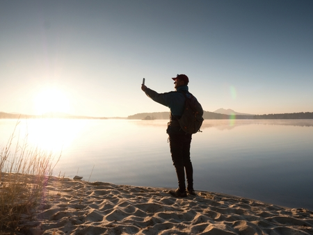 Side View of Man Taking Selfie Photos at the Beach. Hot morning Sun rising over mountain lake.