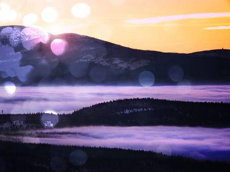 inverse: Film grain effect. Pink orange sun rise above misty winter mountains, shinning fog.  Peaks of  mountains above creamy mist in valley. Stock Photo