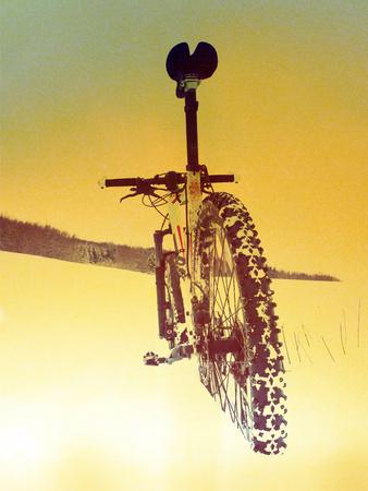 Film grain effect. Mountain bike stay in powder snow. Lost path  in deep snowdrift. Rear wheel detail. Snow flakes melting on dark off road tyre.