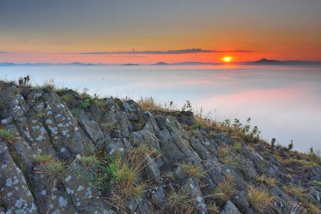inversion: Rocky basalt peak on hill.  Sharp peak of basalt formation. Long basalt poles of cold volcano.  Forest valley full of gentle fog and Sun above heavy mist.