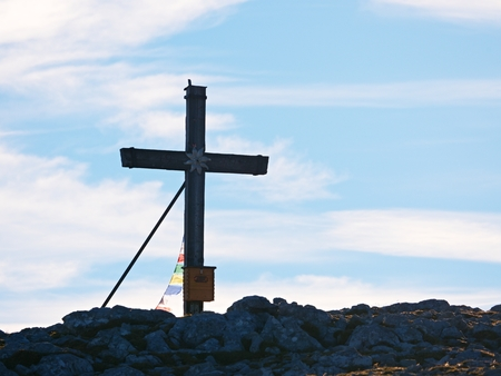 Modest wooden cross  with Buddhist praying flags, raised on rocky Alpine mountain summit . Sharp rocky peak. Gentle clouds  in blue sky. Wooden unpretentious crucifix in memory of victims of mountains. Stock Photo