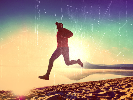 Film grain effect. Sportsman running at amazing summer sunset along coastline in sport and healthy lifestyle concept