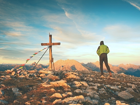 Tourist stand on rocky view point and looking into misty alpine valley. Wooden cross at a mountain peak. Cross on top of a mountain peak as typical in the Alps. Stock Photo