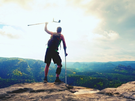 Man with a crutches and a broken leg fixed in a knee brace feature.Traveler with a hurt leg in bandages stay on a rocky view point in the mountains. Hiker with broken leg in immobilizer. Stock Photo