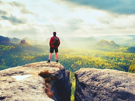 Tall man enjoy freedom on peak of mountain edge. Alone tourist  watching over misty valley to Sun. Beautiful moment in nature.  Short hair man in black pants and t-shirt, summer weather after rain.
