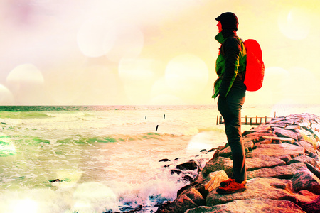 Film grain effect. Tall hiker in dark sportswear with sporty backpack in raincoat  on beach,  horizon with blue sky with clouds. Magic windy day.  Vivid and vignetting effect