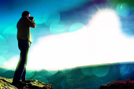 Film grain effect. Professional photographer takes photos with big camera on peak of rock. Dreamy misty landscape, hot Sun above