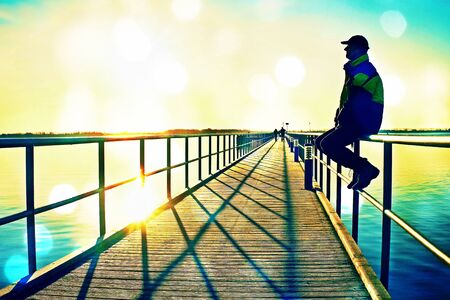Film grain effect. Man in warm jacket and baseball cap sit on pier handrail construction and enjoy morning at sea. Sunny clear blue sky, smooth water level