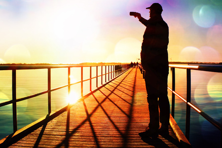 Film grain effect.  Man on pier photograph morning sea. Tourist with smart phone in hand. Fantastic morning with  smooth water level Stock Photo