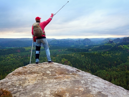 recuperation: Peak triumph. Man with leg in knee cages and crutches for stabilization and walk support. Hiker use adjustable side panels to immobilize and support of hurt knee Stock Photo