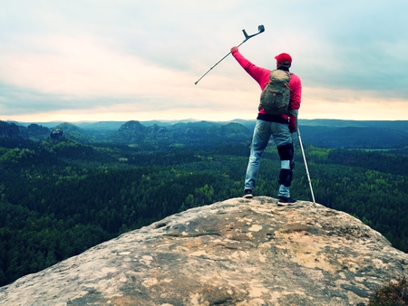 Peak triumph. Man with leg in knee cages and crutches for stabilization and walk support. Hiker use adjustable side panels to immobilize and support of hurt knee Standard-Bild