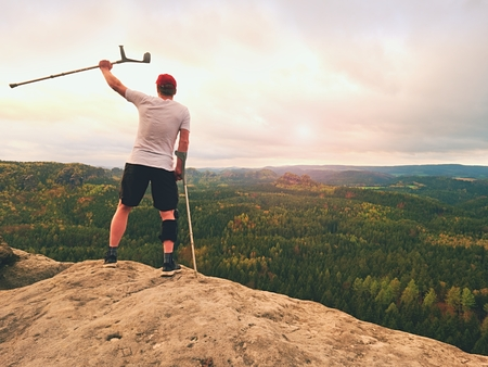 Man tourist after accident use knee brace features  and forearm crutches. Man looking over valley to Sun hang at horizon.