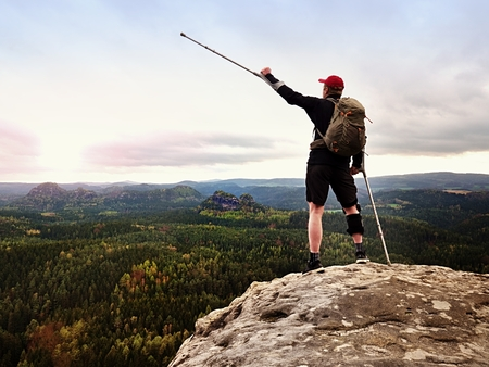 Happy man hiking holding medicine crutch above head, injured knee fixed in knee brace feature. Scenic mountain top with deep cloudy valley below Archivio Fotografico