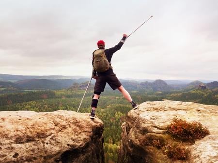 Wandelaar met gebroken been in startonderbreker. Toerist met medicijnpilaar boven hoofd bereikt bergtop. Diep mistige vallei balg silhouet van gelukkig man met hand in de lucht.