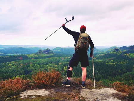 Man hiker Wearing Support Leg Brace and gainst the cruthes. Natural forest park in background Stock Photo