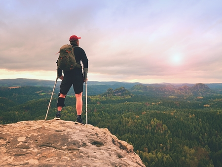 Man hiker Wearing Support Leg Brace and gainst the cruthes. Natural forest park in background Standard-Bild