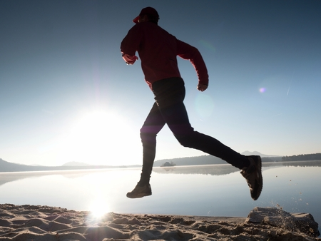 Tall fit man running fast by the sea on the beach. Powerful runner training outdoor in summer morning. Hot Sun is rising up over water level