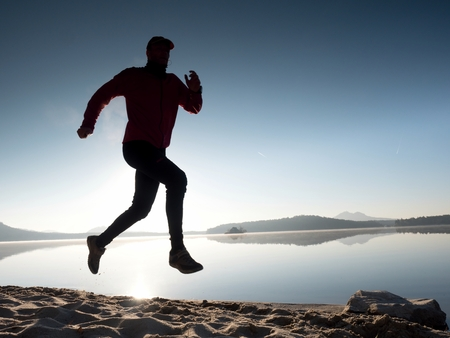Boy running at the beach during sunrise with reflection. Morning bay beach with clear sky. Lens reflections and flare.