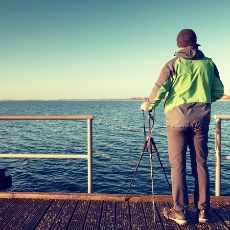 Travel photographer on pier. Photo shooting during sunny autumnal afternoon at handrail on the wooden mole.