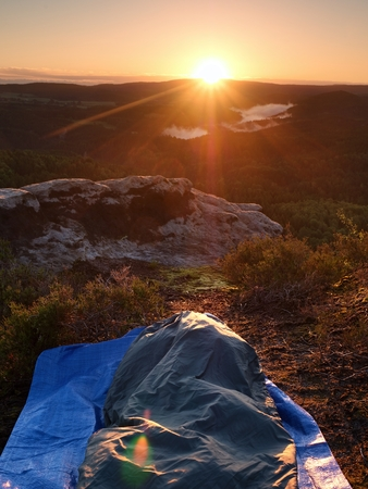 Beautiful awakening in  rocks.  Sleeping in nature in sleeping bag. View from rocky peak over forest valley. Stock Photo
