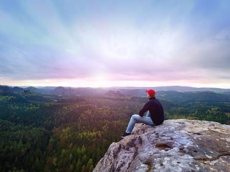 수평선을 찾고. 울창한 숲이나 정글 위의 바위에 앉아있는 사람이보기를 즐긴다. 스톡 콘텐츠