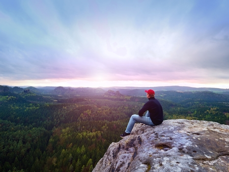Looking to horizon. Man sitting on a rock above the dense forests or jungles and enjoy the view. Фото со стока
