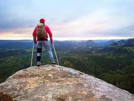 Disabled man with crutches stands on a big rock and looking to mountains at horizon. Hiker silhouette with medicine crutch on mountain peak.