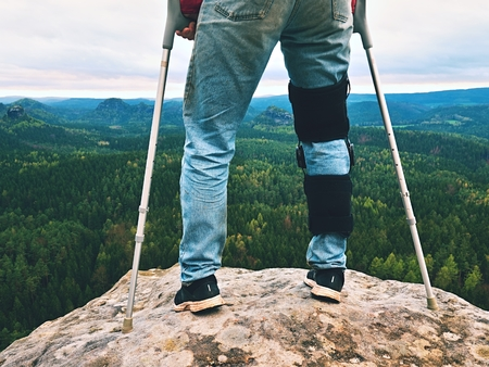 Man with leg in knee cages and crutches for stabilization stay on rock. Hurt tourist walk in mountains, drama view bellow into valley Stock Photo