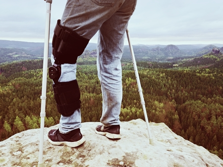 tourniquet: Man with leg in knee cages and crutches for stabilization stay on rock. Hurt tourist walk in mountains, drama view bellow into valley Stock Photo