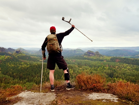weaknesses: Hiker with broken leg in immobilizer. Tourist with medicine crutch above head achieved mountain peak. Deep misty valley bellow silhouette of happy man with hand in air.