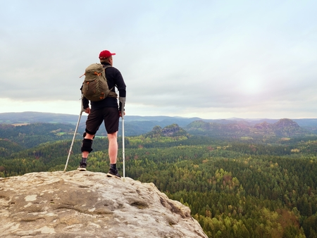 unilateral: Happy man hiking holding medicine crutch above head, injured knee fixed in knee brace feature. Scenic mountain top with deep cloudy valley below Stock Photo