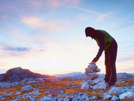 inversion: Alone hiker man on the top of the Alpine mountain building pyrmid from pebbles. Mans hand hold the last stone for the pyramid.  Stones on Alps mountain gravel summit.