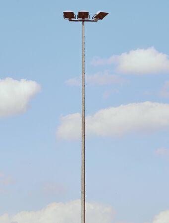 Tall steel  lamp in the park on blue sky in background. High stadium light, spot light pole