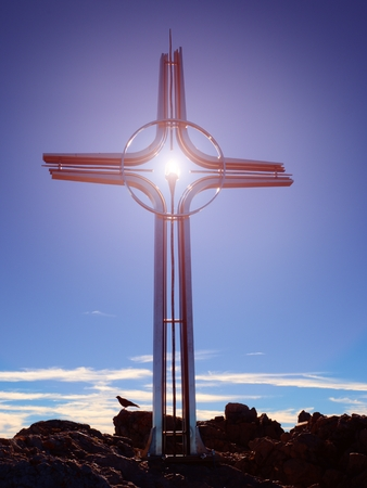 Praying summit cross on high rocky mountain. Steel artistic crucifix on top of Alpine mountain,  in the Dolomite Alps