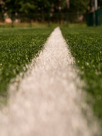 White line marks painted on artificial green turf background. Winter football playground with plastic grass. Play with Depth of Field.