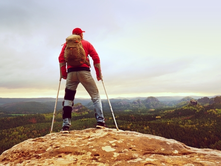 Hiker huts knee. Man with leg in join immobilizer stay on summit and forearm crutches in the air. Hiker achieved mountain peak with broken leg Stock Photo