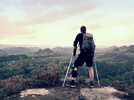 Disabled tourist on crutches on rock. Hurt knee in neoprene metal knee braces and man hold forearms crutches. Stock Photo