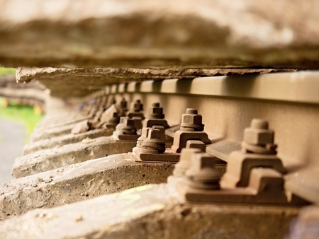 Selective field of focus. Detail of rusty screws and nut on old railroad track. Concrete tie with rusty nuts and bolts. Damaged surface of rail rod. No train passed this railroad for a long time. Stock Photo