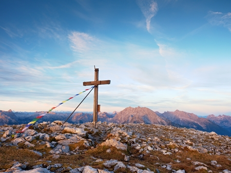 Praying flags fluttering  in the wind on the summit cross. Wooden crucifix on top of Alpine mountain,  in the Dolomite Alps