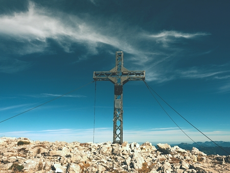 Praying summit cross on high rocky mountain. Steel artistic crucifix on top of Alpine mountain,  in the Dolomite Alps  Stock Photo