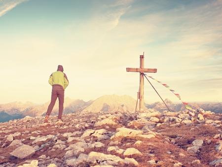 range hood: Man tourist walk to cross on the rocky mountain peak. Evening dark,colorful  sky during sunset.