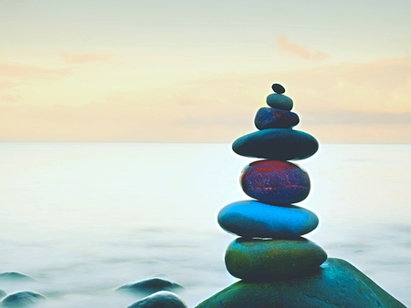 equivalence: Balanced stones, Zen Stack in front of smooth ocean. A calming view from the hotel terrace.