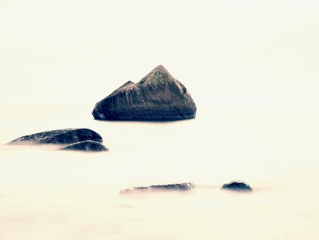 Peaceful morning sea level with stones in peaceful sea level.