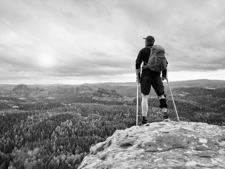 Man hiker Wearing Supportive Leg Brace and gainst the cruthes. Natural forest park in background Stock Photo