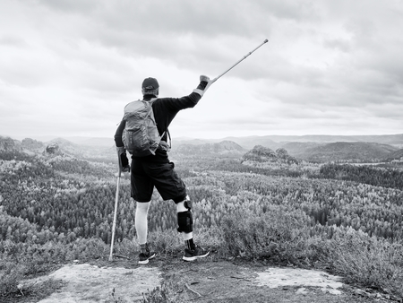 Disabled tourist on crutches on rock. Hurt knee in neoprene metal knee braces and man hold forearms crutches. Stok Fotoğraf