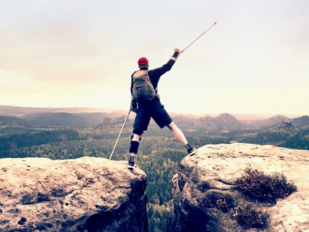 Peak triumph. Man with leg in knee cages and crutches for stabilization and walk support. Hiker use adjustable side panels to immobilize and support of hurt knee Stock Photo